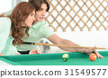 young couple playing billiard 31549577