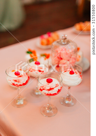 Vanilla pudding in a glass with a cherry 31550800