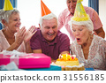 Senior woman blow on birthday cake 31556185