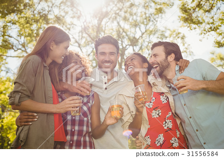 Group of friends holding a glasses of beer in park 31556584