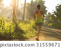 Young fitness woman running at morningforest trail 31559671
