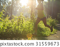 Young fitness woman running at morningforest trail 31559673