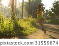 Young fitness woman running at morningforest trail 31559674