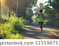 Young fitness woman running at morningforest trail 31559675