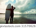 young woman surfer ready to surf on a beach 31570626