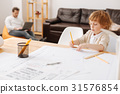 Concentrated kid being busy while working in 31576854