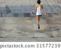 young fitness woman jumping rope on city 31577239