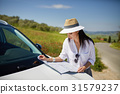 A tourist with a map at the car checks the route to the destinat 31579237