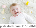Cute baby girl playing with colorful pastel rattle 31585068