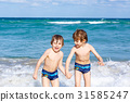 Two kid boys running on ocean beach in Florida 31585247