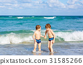 Two kid boys running on ocean beach in Florida 31585266