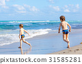 Two kid boys running on ocean beach in Florida 31585281