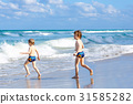 Two kid boys running on ocean beach in Florida 31585282