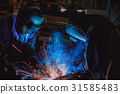 Team workers are welding part in factory 31585483