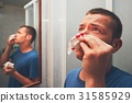 Man with nose bleed 31585929