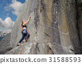 Female climber climbing with rope on a rocky wall 31588593