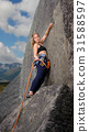 Female climber climbing with rope on a rocky wall 31588597