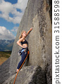 Female climber climbing with rope on a rocky wall 31588598