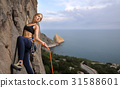 Female climber climbing with rope on a rocky wall 31588601