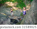 Female climber climbing with rope on a rocky wall 31589025