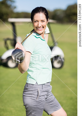 Side view of cheerful woman carrying golf club 31594189