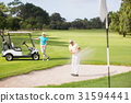 Male golfer playing on sand trap by woman 31594441
