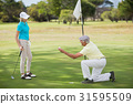 Mature man holding golf ball by woman 31595509