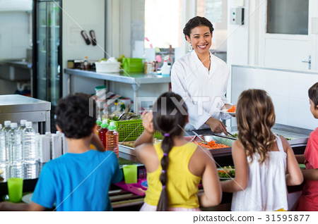 Woman serving food to schoolchildren 31595877