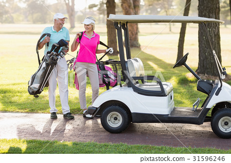 Happy mature golfer couple by golf buggy 31596246