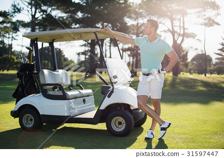 Full length of man by golf buggy 31597447