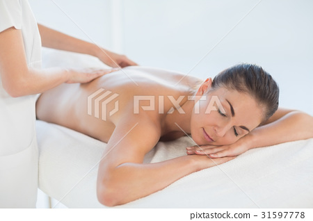 Relaxed naked woman receiving back massage 31597778