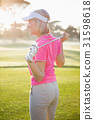 Side view of woman golfer holding her club 31598618