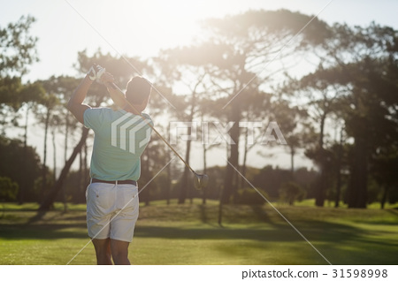 Rear view of young golfer taking shot 31598998