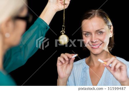 Hypnotherapist holding pendulum by patient 31599487