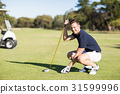 Side view of man placing golf ball on tee 31599996