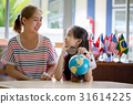 Asian family learning a globe by magnifying glass 31614225