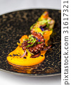 Tentacles of an octopus on a mango puree 31617321