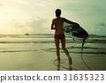 young woman surfer ready to surf on a beach 31635323