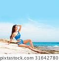 Young brunette woman in a bikini on the beach 31642780