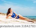 Young brunette woman in a bikini on the beach 31642783