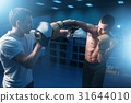 Boxer in gloves exercises with personal trainer 31644010