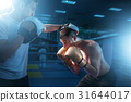 Boxer in gloves exercises with sparring partner 31644017