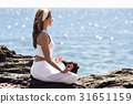 Young woman doing yoga in the beach wearing white clothes 31651159