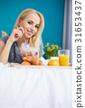 Pretty young blonde woman enjoying a breakfast of fresh crisp cr 31653437