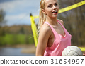 Joyful sexy blond girl playing volleyball outdoors on the lakesi 31654997