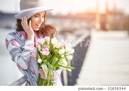 Young woman with a bouquet of tulips at the street. 31656344