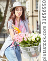 Joyful stylish woman in gray hat  on a bicycle with juice, pink 31656550
