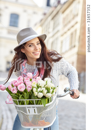 stylish woman in gray hat on a bicycle with spring flowers on a 31657352