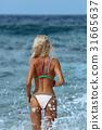Back view of sexy woman in bikini walking in water 31665637