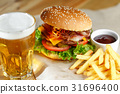 Big tasty burger and fries with beer on foreground 31696400